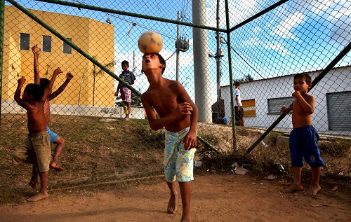 Rio de Janeiro, Brazil August 26, 2012 Children play soccer on a dusty field in the Palmeiras favela. Nearly half of Brazil's population is under 24 years of age. There are supreme challenges facing the country as the economy grows yet educational resources remain far behind, especially in the favelas.
