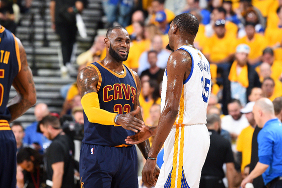 OAKLAND, CA - JUNE 1: LeBron James #23 of the Cleveland Cavaliers and Kevin Durant #35 of the Golden State Warriors high five each other during Game One of the 2017 NBA Finals at Oracle Arena on June 1, 2017 in Oakland, California. NOTE TO USER: User expressly acknowledges and agrees that, by downloading and/or using this Photograph, user is consenting to the terms and conditions of the Getty Images License Agreement. Mandatory Copyright Notice: Copyright 2017 NBAE (Photo by Andrew D. Bernstein/NBAE via Getty Images)
